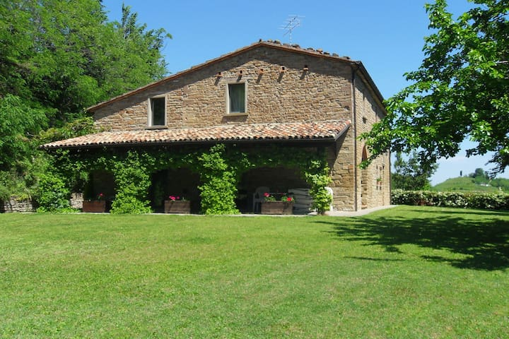 Stone house in the green rolling hills of the Apennines with garden.