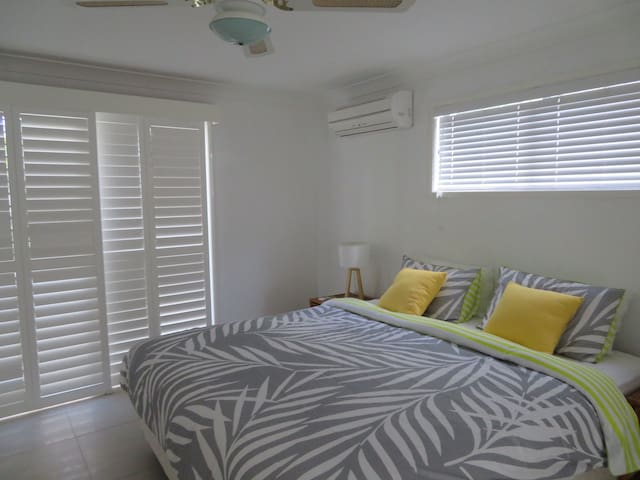 Spacious master bedroom with A/C & WIR and large disabled en-suite - screened doors leading out to the yard.