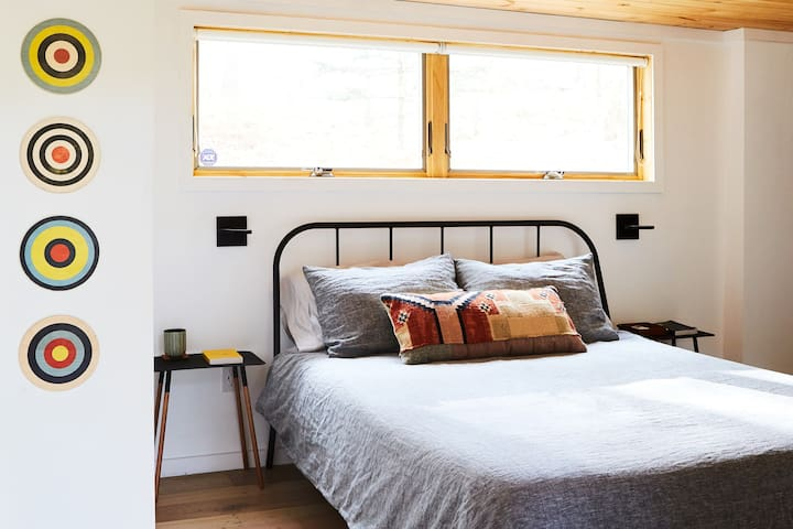 Ground level master suite, queen bed, closet, hangers, bench, and heating+AC unit.