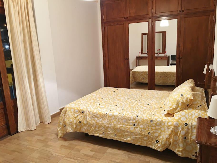 Dormitorio principal con cama doble, amplio armario y balcón.