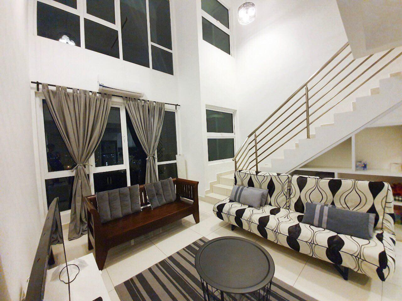 Lounge area with sofabed; storage behind the sofabed; stairs up to the bedroom