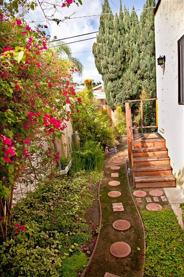 Up the garden path to your door at the top of the stairs. Five steps up into the room.  Pathway is sand and round stones.