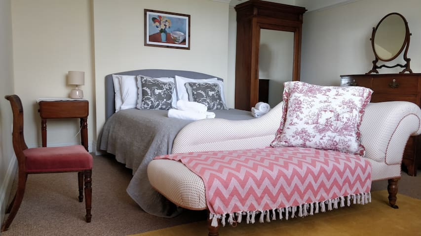 Bedroom 1 with king-size bed and ensuite bathroom. Stunning view of the Cotswolds hills and the Berkeley Castle water-meadows.