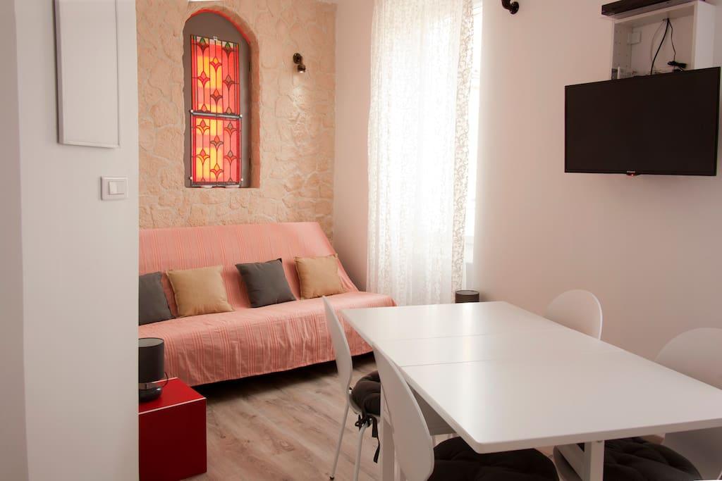Le salon, avec le canapé lit. L' éclairage du vitrail peut changer de couleurs en fonction des goûts ..