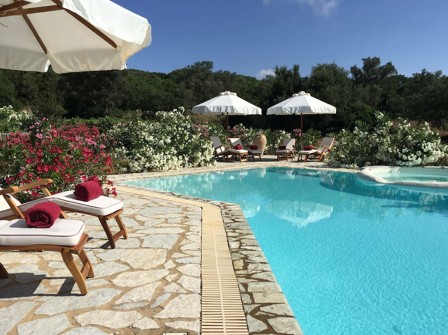 Your private terrace around the swimming pool with teak deckchairs