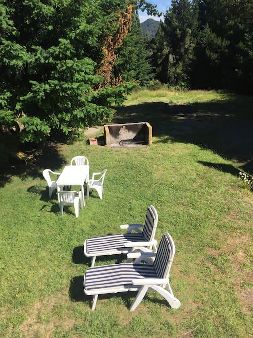 Parrilla, mesas, y reposeras en el jardin