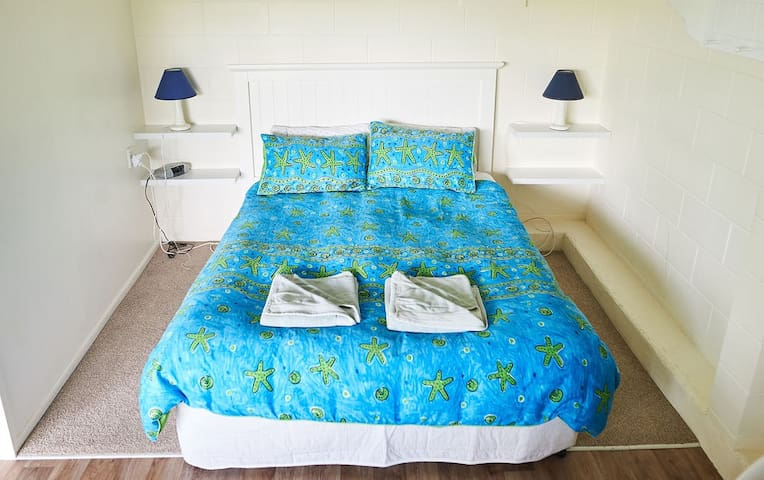 Queen Size bed, side lamps and digital clock radio