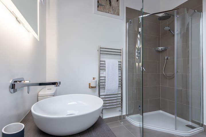 Shower, washbasin and Victoria and Albert bath in both en-suite bathrooms.