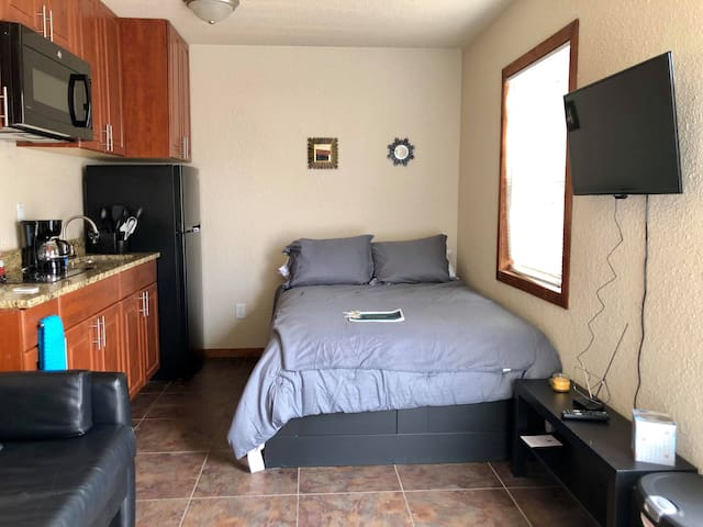 Small living room area with TV (antenna). Microwave, coffee maker, full size fridge. Couch and full size bed.