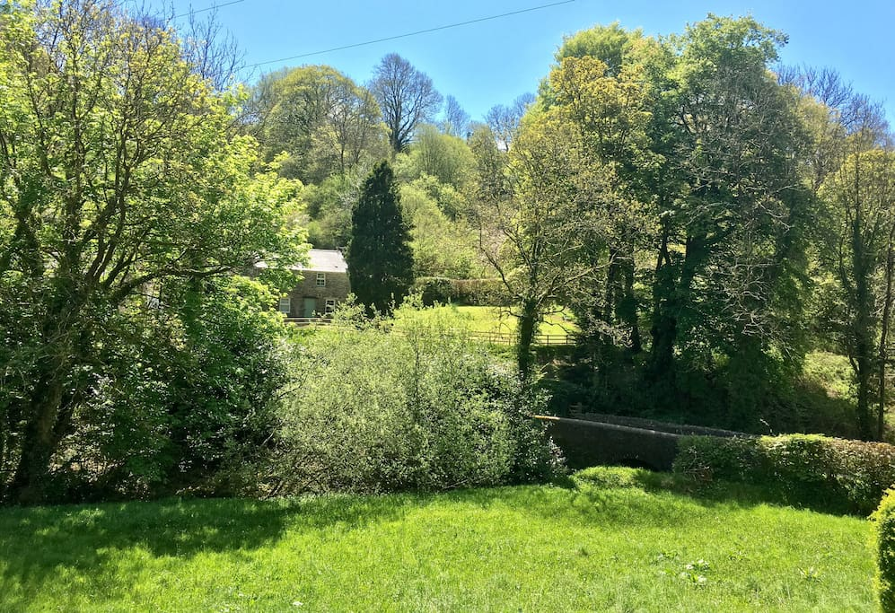 Cottage is nestled in picturesque valley overlooking stone bridge.
