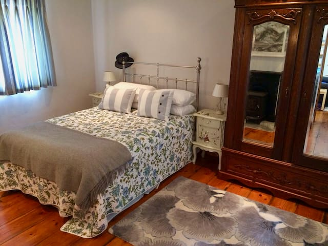 Guest bedroom with queen-sized bed, wardrobe, wood-burning stove.