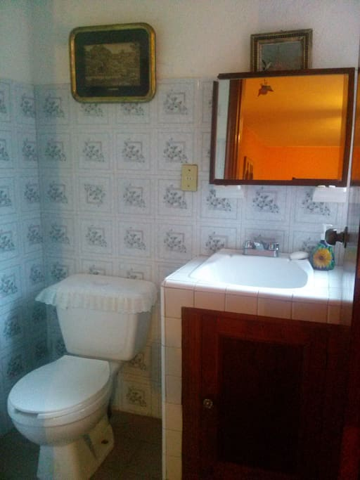 El medio baño está fuera de la habitación pero está disponible para los huéspedes.