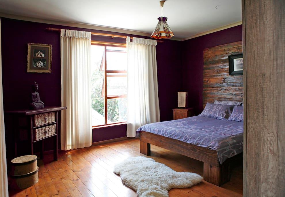 Upstairs main bedroom with garden view,queen size bed,en suite bathroom and sliding door leading to covered deck area