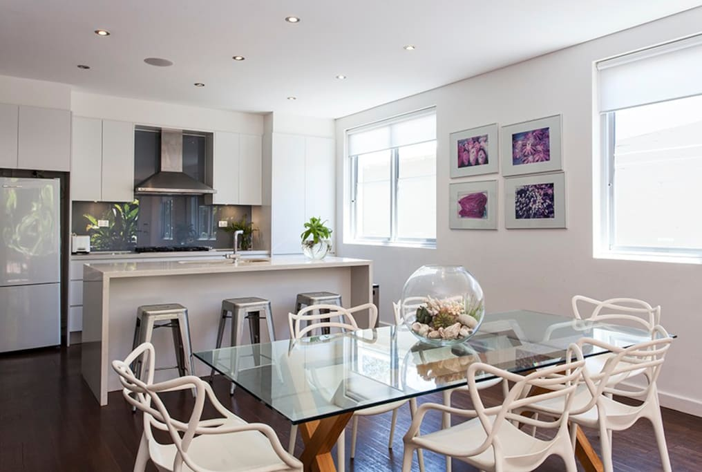 Kitchen and dining area, with bar stools. Main living space flows from kitchen to dining and onto seating area.