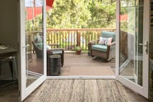 French doors open to the deck furnished with comfy armchairs.