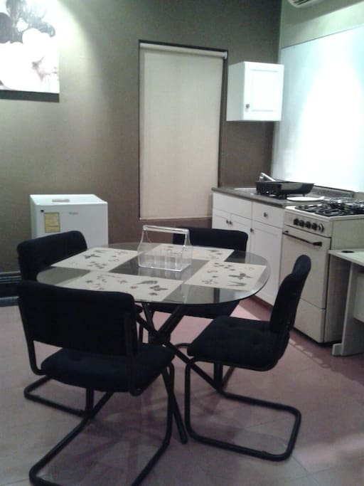 In apartment 2, there is a kitchenette with a mini fridge, a sink and 2 electric burners. There is also a microwave, a coffee pot, a toaster and a kitchen cabinet with 1 drawer with table ware, There is no oven available. There is also a small round table with chairs.