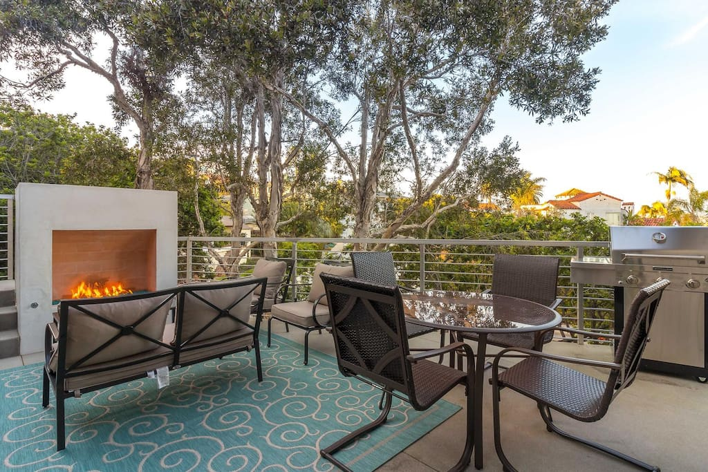 Enjoy a cup of coffee while warming up by the custom modern outdoor fireplace and patio furniture