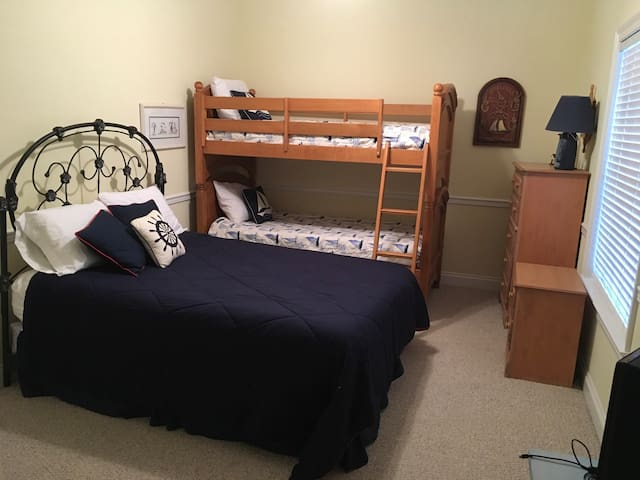 This bedroom sleeps 4. There are bunk beds and a queen bed. Has a flat screen tv