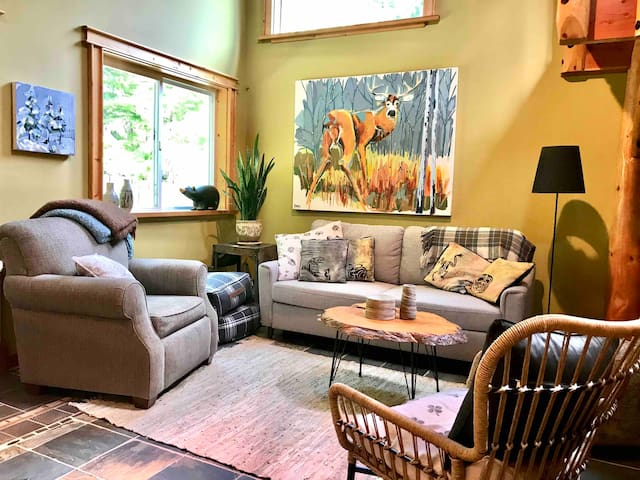 Bright living room looks out to trees with 23 ft. high ceiling, comfy pullout sofa.
