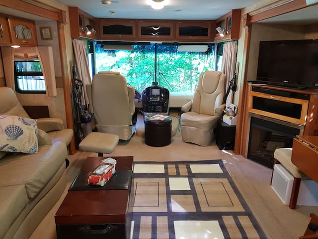View through front window of motorhome showing TV, VCR and electric fireplace on the right.