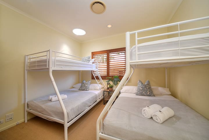 Bunk room with A/C has two double beds and two single beds. There is a skylight above one of the top bunks.