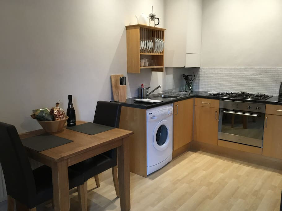 Fully equipped kitchen with washing machine, fridge, cooker and microwave.