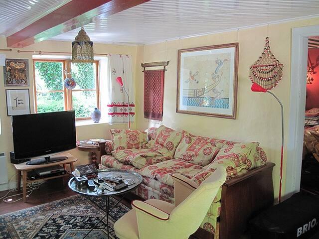 Trivsamt vardagsrum med bjälkar i taket och kamin