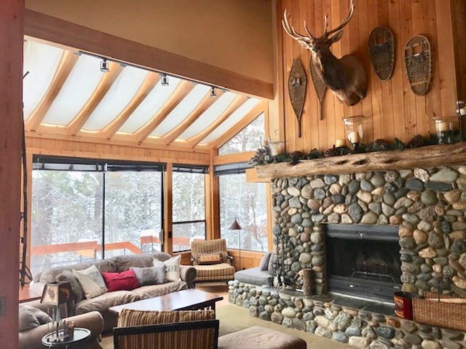 Sun-drenched living room with rustic stone fireplace