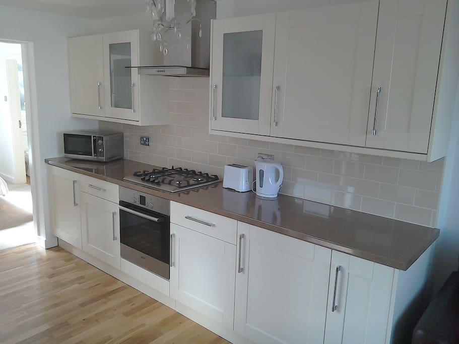 Well equipped kitchen including Bosch oven and hob, integrated fridge, washing machine, microwave, kettle and toaster.