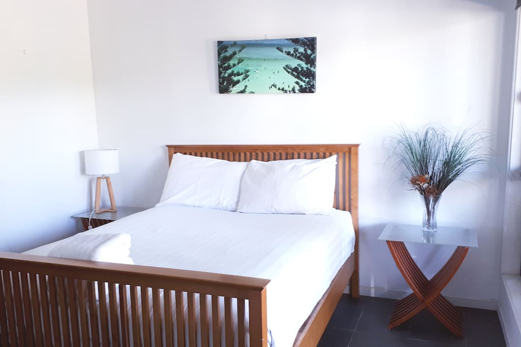 Comfortable double bed in clean, bright bedroom.