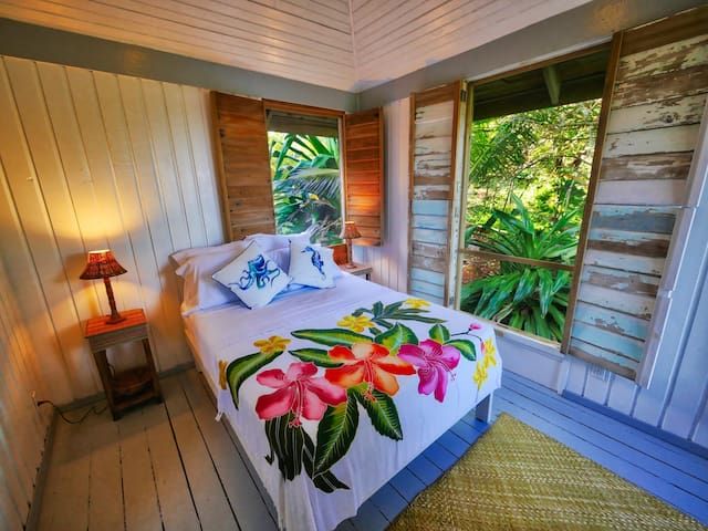 Dreamy queen bed surrounded by views of Roatan's jungle and sea.