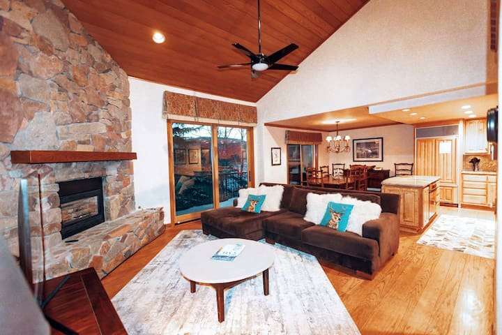 Spacious Living area with river rock, gas fireplace, velvet sectional, velvet recliner, ceiling fan, giant screen smart TV & wet bar. Town of Vail STR Permit # 025978.
