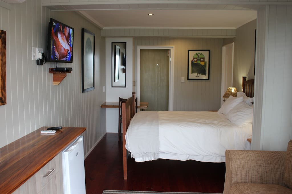 Full view of newly renovated luxury room from entrance and deck, antique double teak bed with firm, foam mattress, coffee station with fridge, couch , HD flat screen TV for viewing of your favourite DStv channels, writing desk, build-in cupboard, original art work by South African artist