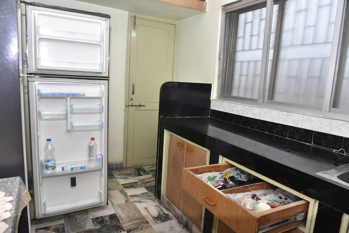 The kitchen is equipped with basic cooking utensils, a hot plate, cutlery, plates, bowls, and a fridge to store your food.