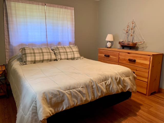This Bedroom has a queen size mattress, dresser, night stand, and a double length closet