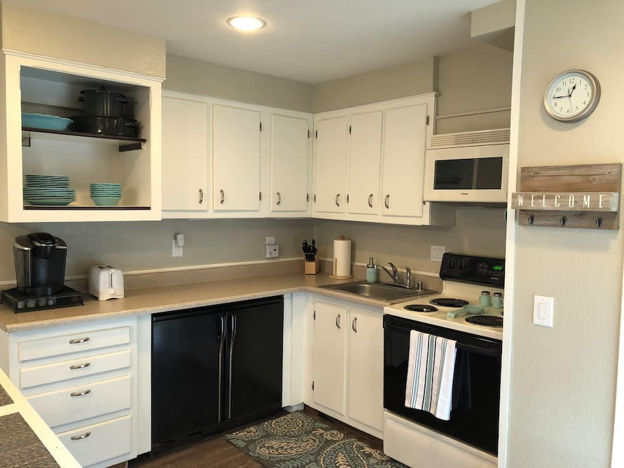 "The kitchen features an oven, electric stove, microwave, Keurig, and toaster.  The bonus is an under-counter ""beer fridge"" and freezer."
