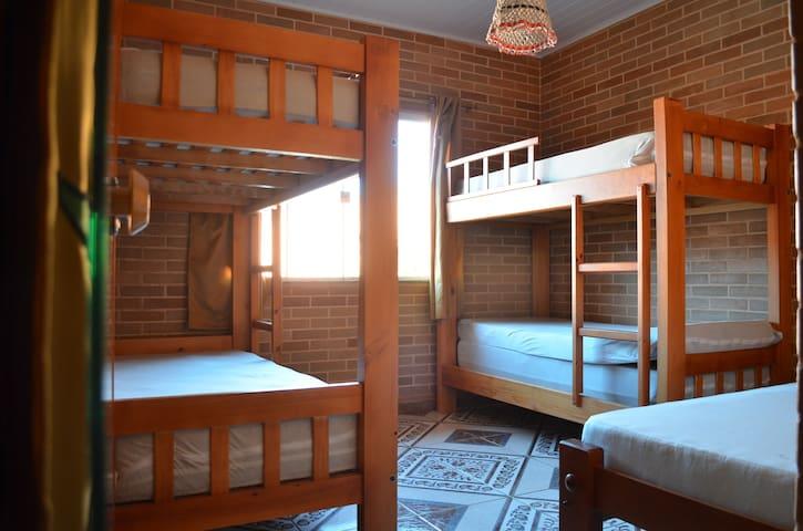 Quarto com duas beliches e uma cama de solteiro.