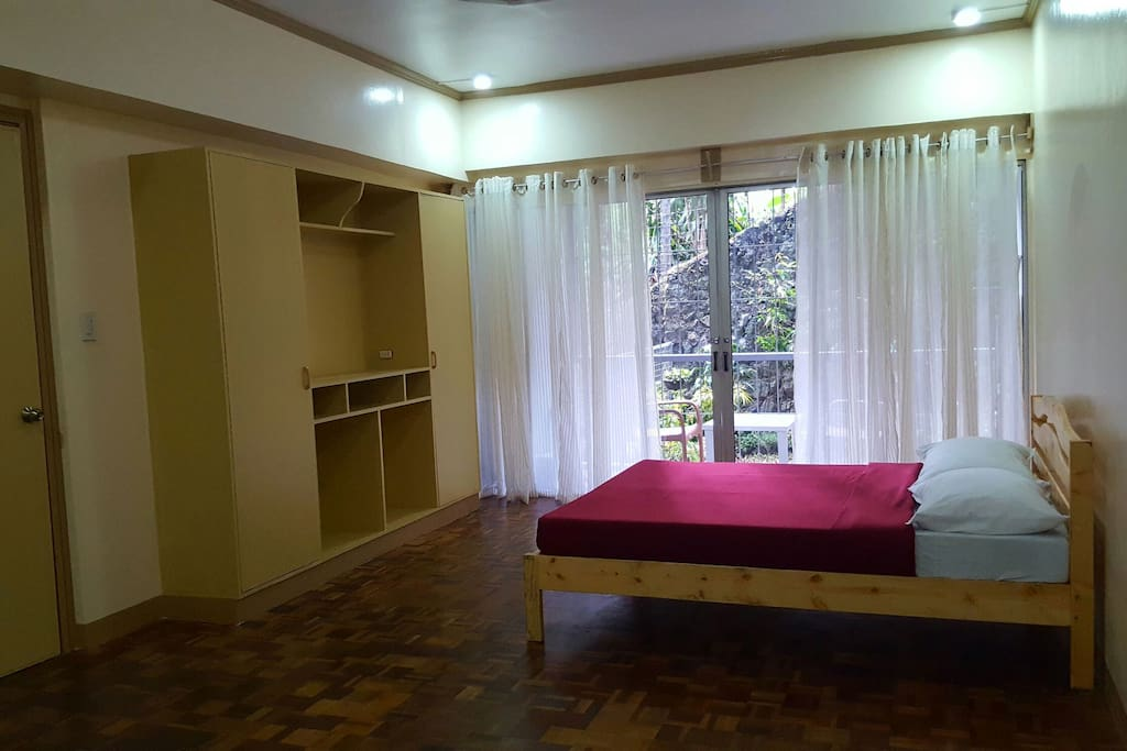 Master bedroom. With queen-sized bed, own toilet and bath, and closet. Spacious -  it could accommodate 4 more single mattresses. Sliding doors open to the balcony and small private garden.