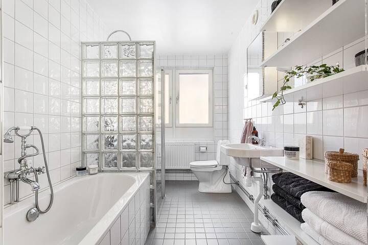 Badrum med dusch, badkar och tvättmaskin