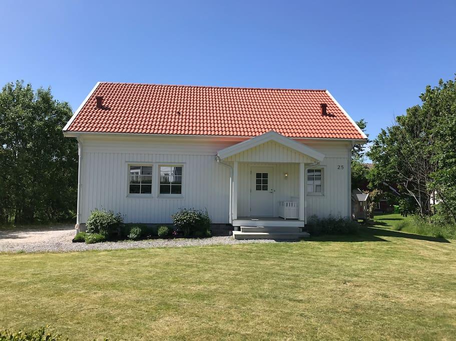 Huset från framsidan med stora trädgårdsytor.