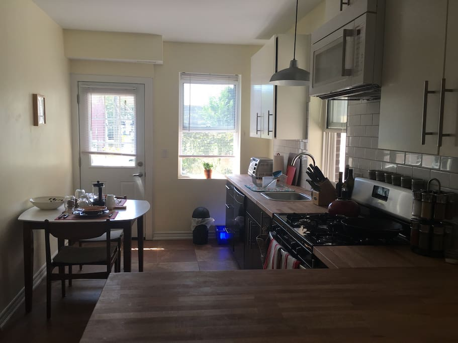 Bright open equipped kitchen with gas stove, butcher block counter tops and large dishwasher.