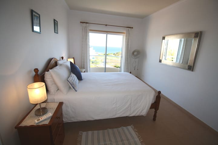 The master bedroom has doors to the veranda with sea and pool views