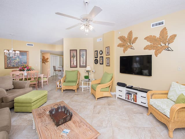 """In the living area, relax on the couch or wicker chairs in front of the 65"""" flat-screen TV."""