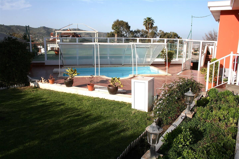 Amplia piscina con solarium rodeado de zonas ajardinadas y vistas a la costa