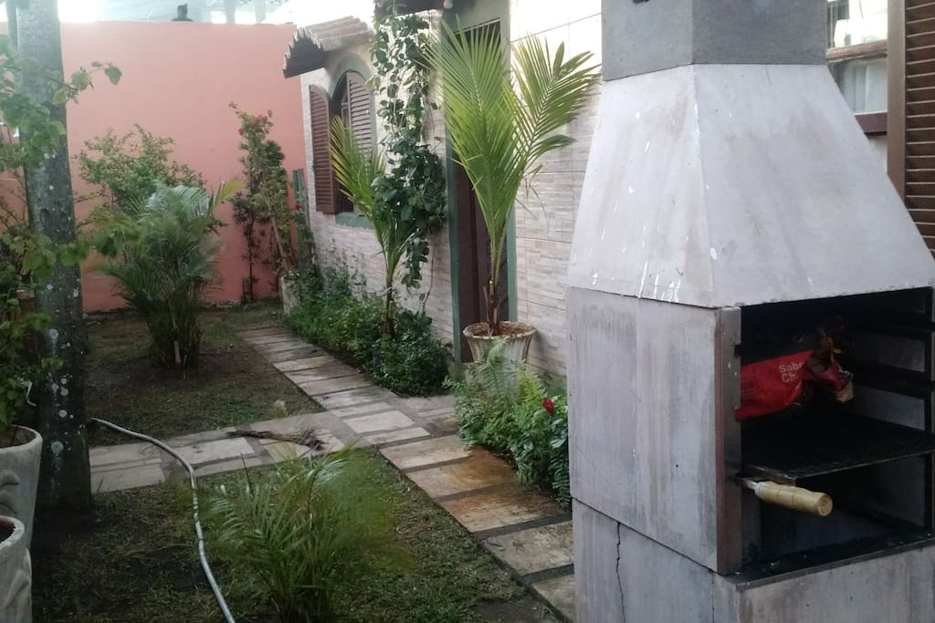 Jardim e churrasqueira na entrada da casa