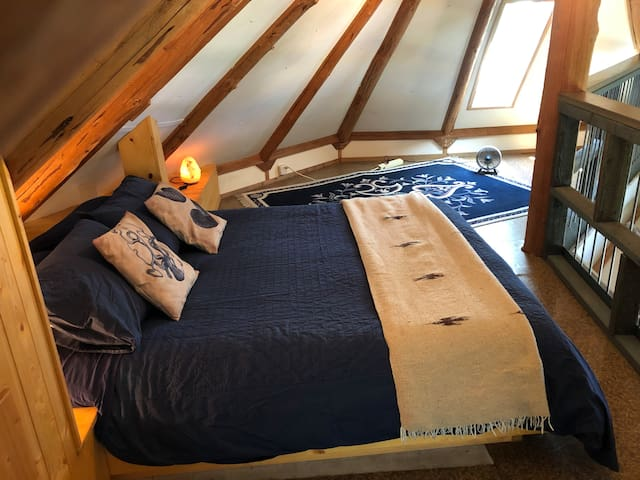 Sleeping loft with queen bed, skylights and library, and view of the water from your pillow!