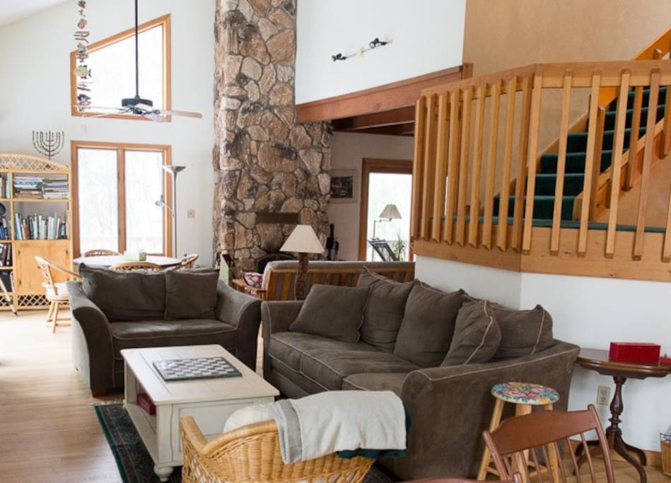 Open floorplan features a working stone fireplace, comfy couches, and plenty of space to gather.