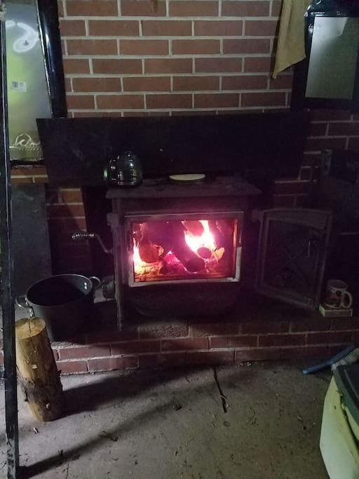 Woodstove has a screen so you can see full fire or close doors to cook.