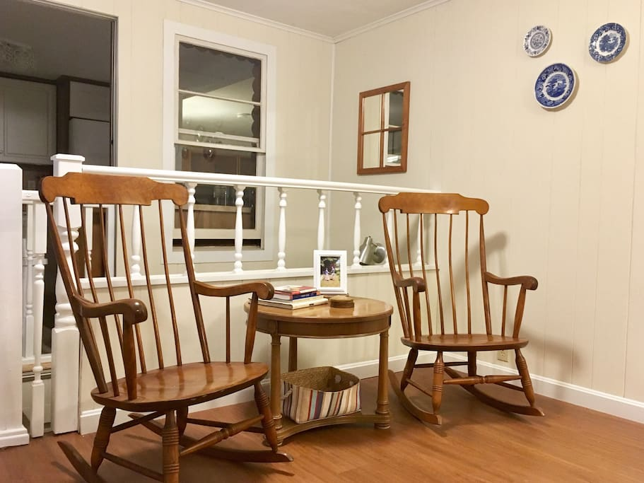 The rocking chairs are facing the window that overlooks the backyard.