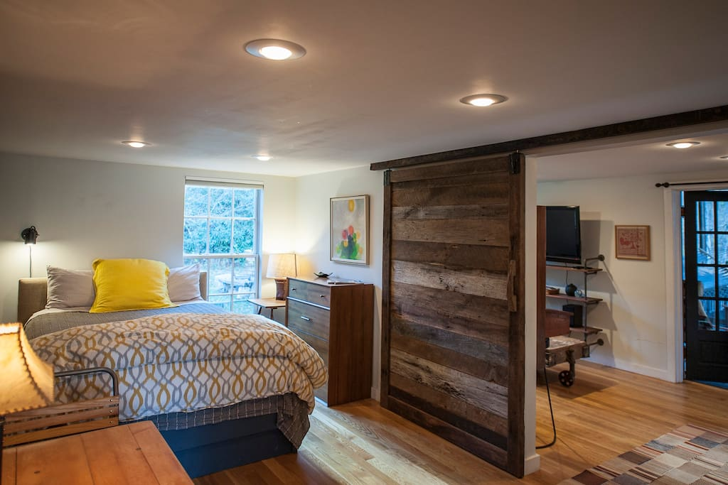 Beautifully decorated bedroom with new queen bed, sliding barn door to living room.